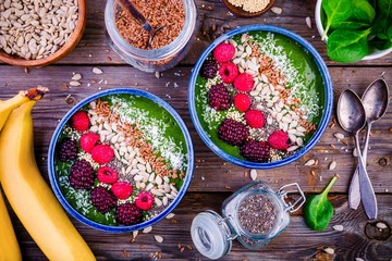 Green spinach smoothie bowl with raspberry,.blackberry,.flax seeds, sunflower seeds and coconut chips