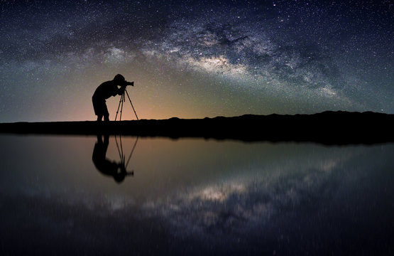 Landscape with Milky way galaxy. Night sky with stars and silhouette Photographer take photo on the mountain.