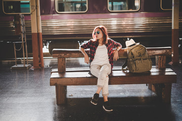 Young hipster woman waiting on the station platform with backpack. Travel concept.