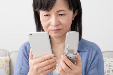 携帯電話を見る女性、スマートフォン、フィーチャーフォン、悩む