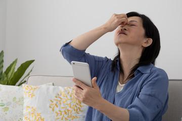 携帯電話を使う女性、眼精疲労