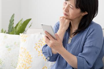 携帯電話を使う女性、困る、考える、悩む