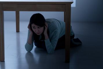 テーブルの下に隠れる女性、地震、震災、災害