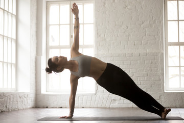Young attractive yogi woman practicing yoga concept, standing in Side Plank exercise, Vasisthasana pose, working out, wearing sportswear, full length, white loft studio background, side view
