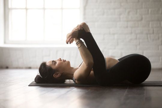 Young attractive yogi woman practicing yoga concept, lying in Happy Baby exercise, Ananda Balasana pose, working out, wearing black sportswear, full length, white loft studio background, side view