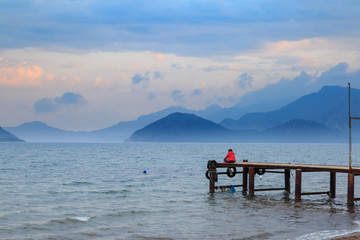 Lonely woman sitting on pier during sunset in marmaris, turkey