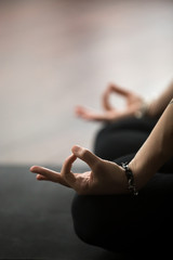 Mudra gesture performed with female fingers, woman meditating in lotus pose, sitting in Padmasana exercise, studio or home background, vertical photo. Meditation session concept. Copy space. Close up