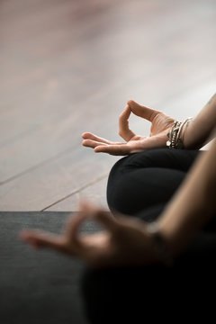 Close up of mudra gesture, performed with female fingers, yogi woman meditating in lotus pose, wearing wrist bracelet, sitting in Padmasana exercise, vertical photo. Meditation session concept