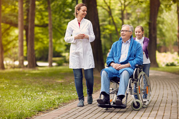 elderly man on wheelchair with nurse and granddaughter outdoor.