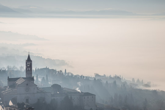Beautiful view of the St. Clare church in Assisi (Italy) with fog below and in the background