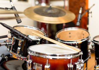 A view of a drum kit set up for recording in a recording studio with microphones in place