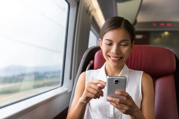 Happy Asian businesswoman using mobile phone app to text sms message or play video games while commuting to work in train. Woman sitting in transport enjoying travel.