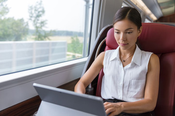 Businesswoman working on laptop on train. Asian freelance writer or designer writing emails on computer while commuting to meeting in the city. Commuter woman urban travel.