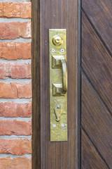 bronze handle on a wooden door