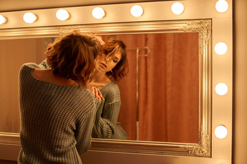 One sexy girl with flowing brown hair of curls in a knitted sweater passion posing with gentle hands near mirror with golden frame lamps light interior fashion photo
