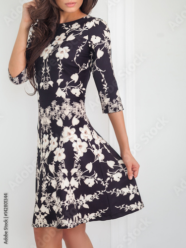 Young fashionable brunette woman in short black and white dress with floral  pattern posing 0247707e6
