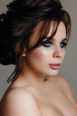 Beautiful, tender, sexy brunette Girl with long hair and puffy lips with makeup, creating on a gray background. Soft focus, space for text