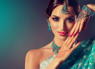 Portrait  smiling of beautiful indian girl. Young indian woman model with blue kundan jewelry set . Traditional Indian costume  .  Wall mural