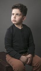 Small boy sitting on wooden box in dramatic pose