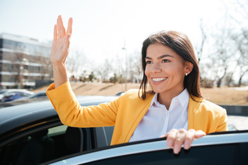 Successful businesswoman standing near the car and waving her hand