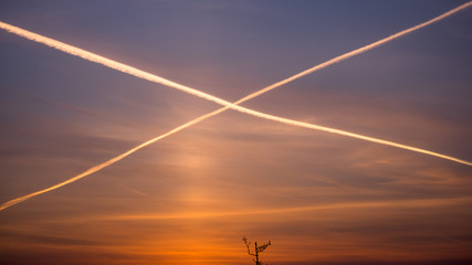 Cross from airplanes' gases on the morning sky