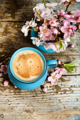 Morning coffee with pink blossom on old wood table