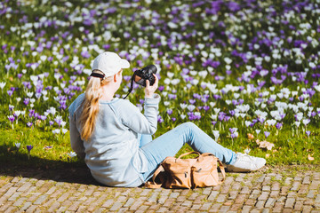Woman with cap taking pictures of crosuses in grass.