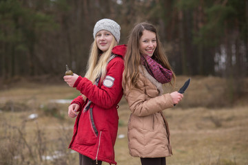 The brunette in her hand holds a knife, and the blonde, dressed in a red jacket, holds a grenade in the autumn or winter forest