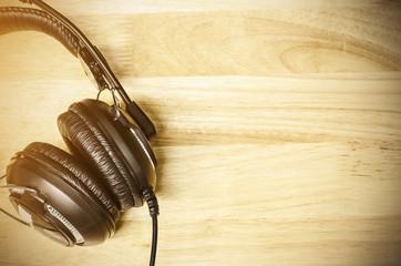 Headphones on wooden desk table. Top view