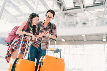 Asian couple travelers using smartphone checking flight or online check-in at airport, with passport and luggage. Air travel or mobile phone technology concept