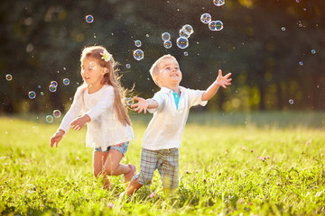 Cheerful children chase bubbles