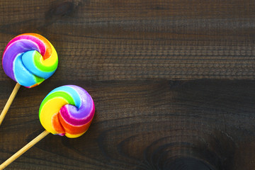 two rainbow colored lollipops on blue wooden background. Copy space. Top view.