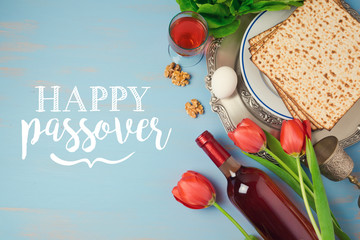 Jewish holiday Passover Pesah greeting card with seder plate, matzoh and flowers over blue background. View from above