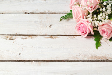 Background with rose flowers bouquet on wooden vintage table