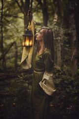 Beautiful woman in a forest with a lantern