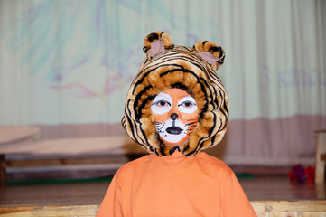 tiger costume for school performance. mask for child.Children face painting. Boy  painted as tiger or ferocious lion. Boy actor playing role. theatrical tiger mask face. School activity