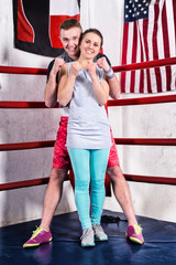 Pair in sportswear standing in a boxing pose in regular boxing ring