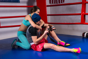 Young sporty woman support and hug male boxer in a boxing ring