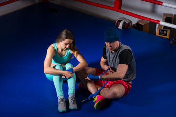 Male sporty boxer preparing bandages sitting near athletic female