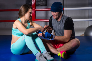 Male sporty boxer helping to prepare  bandages athletic female