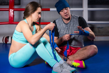 Athletic young boxing couple preparing bandages