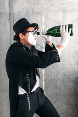 Pantomime theater actor performing with big bottle