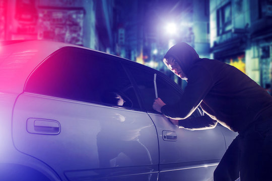 car thief in action at night. Car Security Theme.