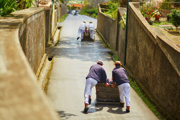 Toboggan riders pushing wooden sledge downhill in Funchal, Madeira island, Portugal Fototapete