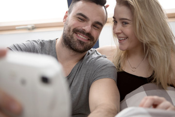 Couple taking selfie with instant camera at home.