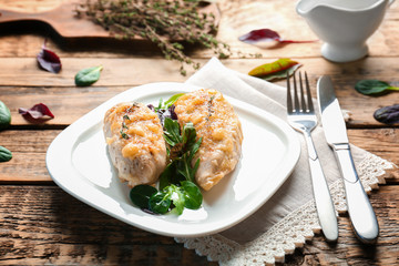 Plate with delicious chicken breasts on wooden table