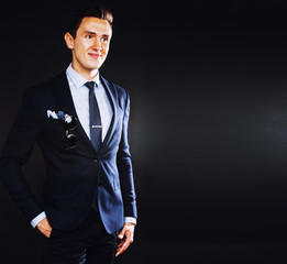 young pretty business man standing on black background, modern h