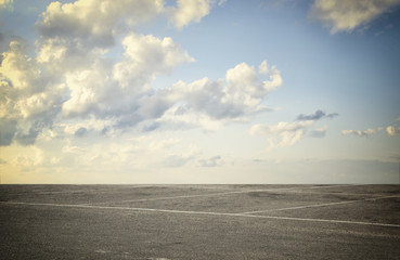 image of asphalt road and clear blue sky with clouds at horizon