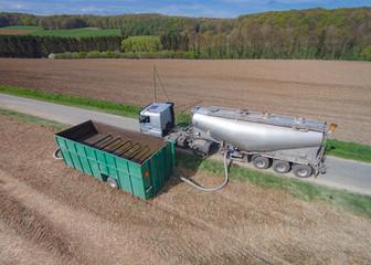Gülletransporter betankt einen Zwischenbehälter am Ackerrand für die Gülleausbringung