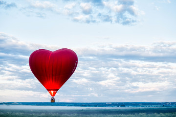 Red air balloon heart rises up at dawn